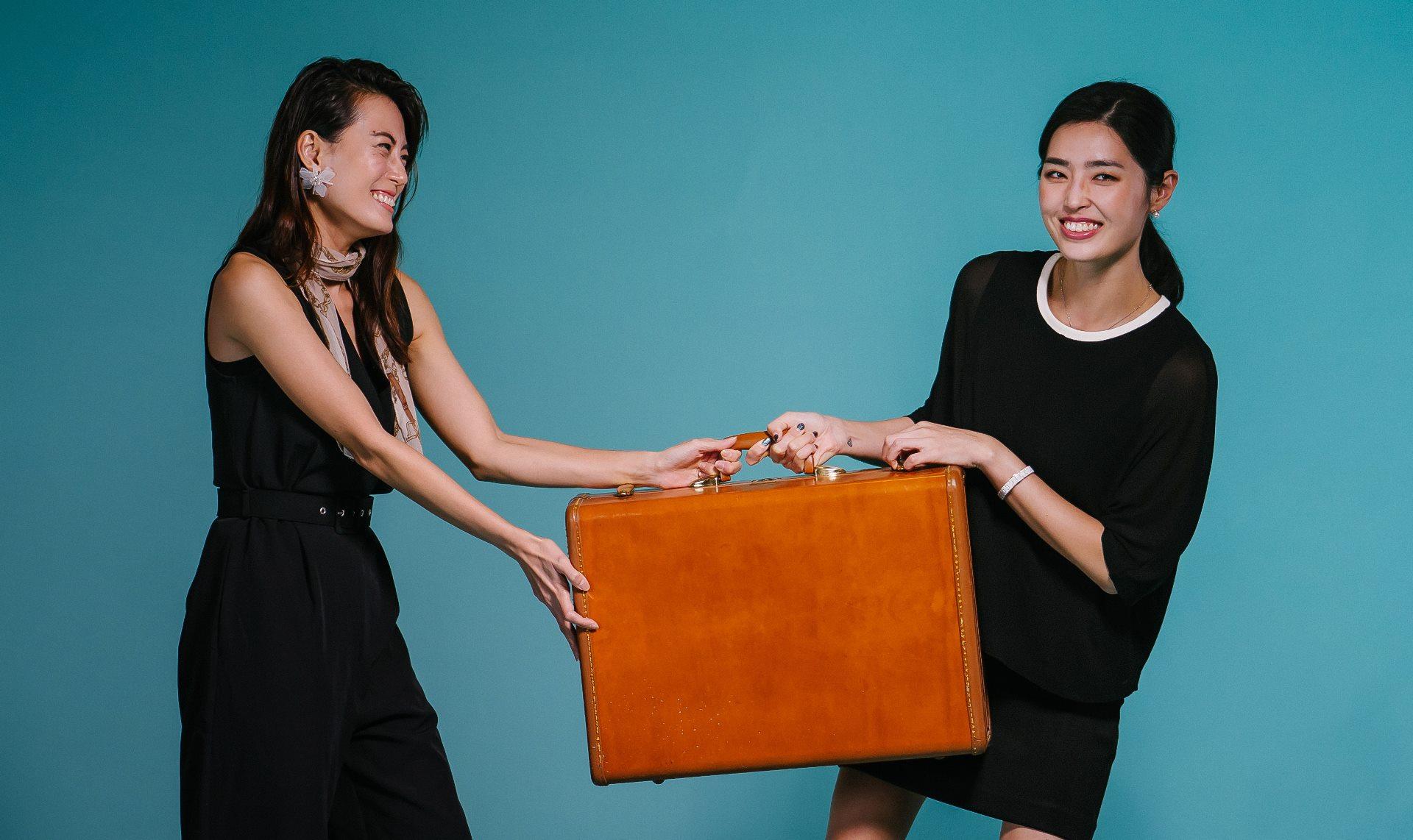 Frauen ziehen an einem Koffer- teilen geht einfacher